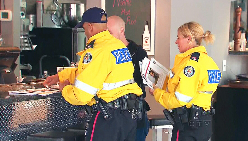 Police hand out flyers related to the disappearance of three men in the neighbourhood of Church and Wellesley, in Toronto, Thursday, June 6, 2013.