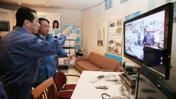 Japanese Prime Minister Naoto Kan, left, listens to an employee of Tokyo Electric Power Co. as he visits J-Village, a national training center at Naraha town, Fukushima Prefecture, northeastern Japan, Saturday, April 2, 2011. (AP / Prime Minister's Office of Japan)