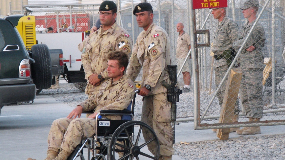 Pvt. Glen Kirkland, in wheelchair, one of five soldiers injured in a direct fire explosion earlier, attends the ramp ceremony for fallen comrades in Kandahar, Afghanistan, Wednesday, Sept. 4, 2008. (Tobi Cohen / THE CANADIAN PRESS)