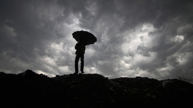 A boy walks with an umbrella to protect himself from the rain, as dark clouds hover over him in Jammu, India, Wednesday, March 9, 2011. (AP Photo/Channi Anand)