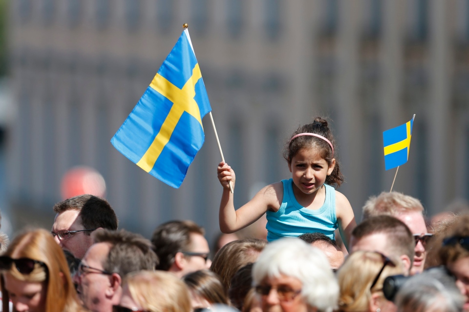 A girl waves with a Swedish flag outside the Royal castle where Princess Madeleine of Sweden will marry New York banker Christopher O'Neill in the Royal church later in the day in Stockholm, Saturday, June 8, 2013. (Bertil Enevåg Ericson / SCANPIX)