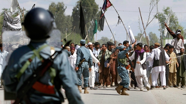 Afghan policeman try to control protestors during a demonstration in Laghman east of Kabul, Afghanistan on Monday, April 4, 2011. (AP / Rahmat Gul)