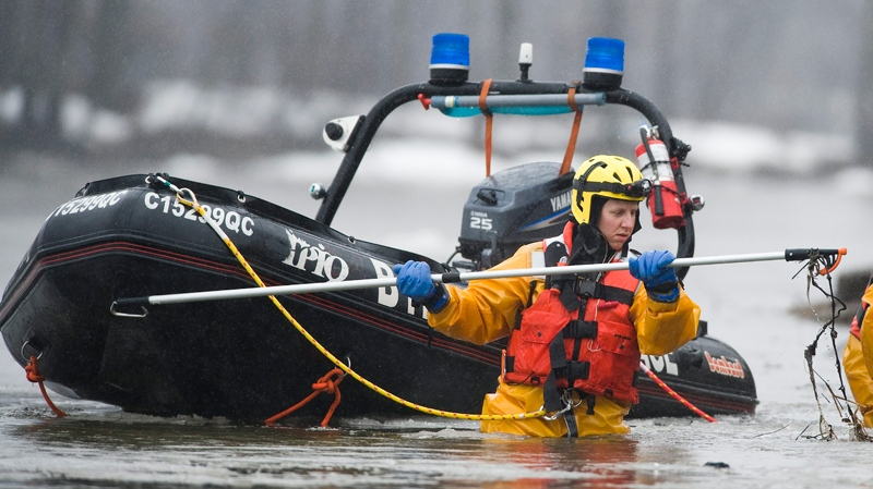 A provincial police rescue searcher combs a river close to a wooded area in Laval, Que., near Montreal, Monday, April 4, 2011. (Graham Hughes / THE CANADIAN PRESS)