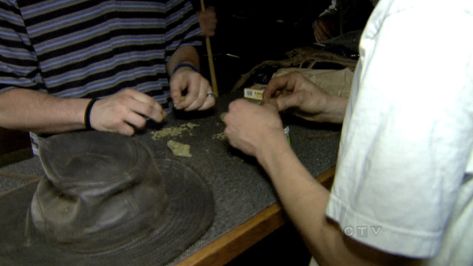 Patrons at Frankie's Sports Bar in Olympia, Washington, roll joints after a game of pool.