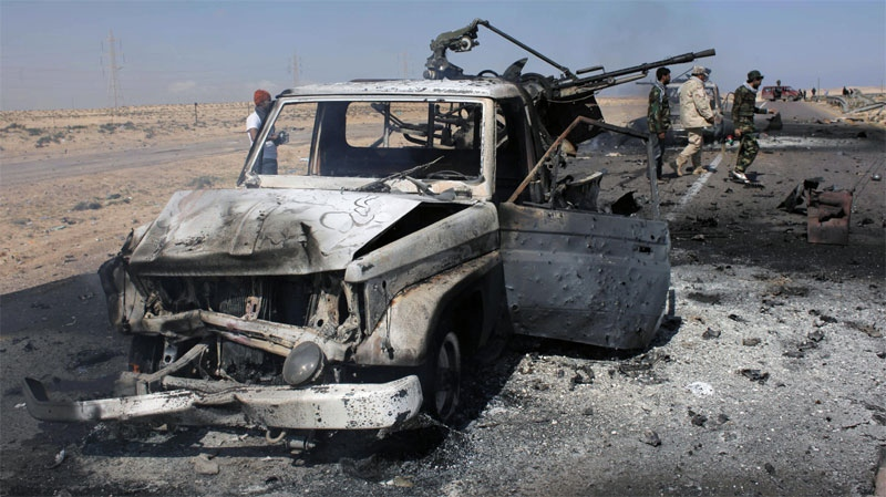 Libyan rebels inspect two destroyed military vehicles of pro-Gadhafi forces that rebels claim were targeted by a NATO strike along the front line near Brega, Libya Tuesday, April 5, 2011.  (AP / Nasser Nasser)