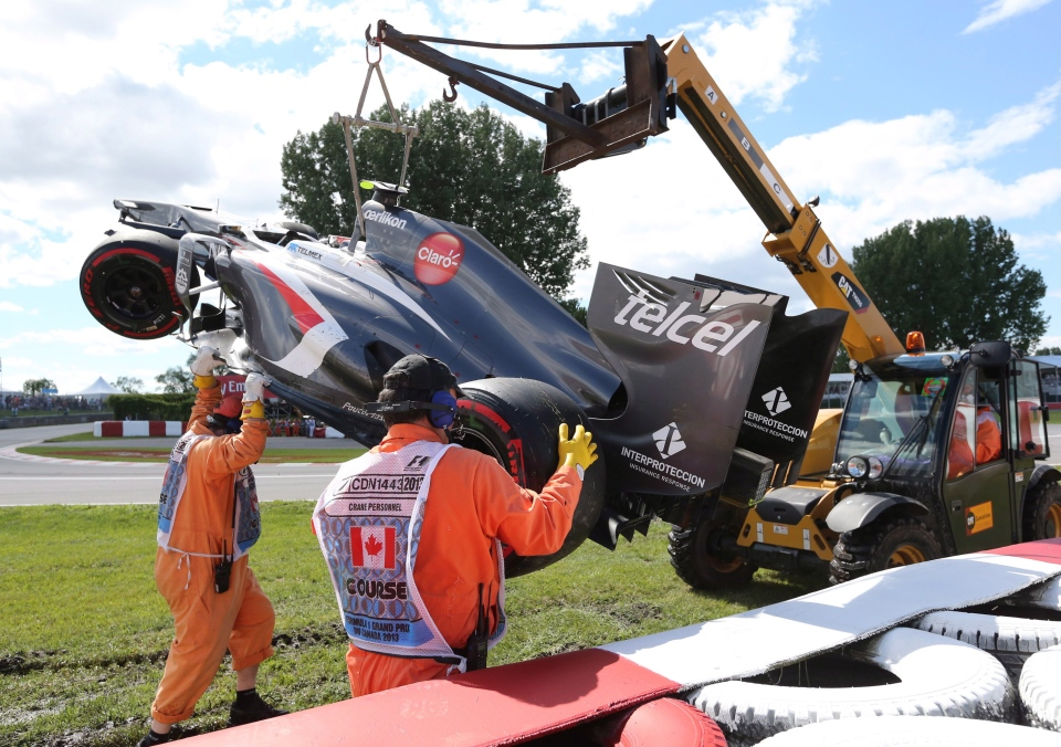 Track workers remove the car of Sauber driver Esteban Gutierrez of Mexico ater a crash at the Canadian Grand Prix, Saturday, June 8, 2013 in Montreal. A worker was seriously injured when he was run over by the tractor. (Tom Boland / THE CANADIAN PRESS)