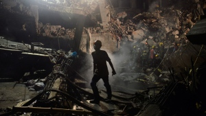 A Bangladeshi worker leaves the site where a garment factory building collapsed in the Savar area on the outskirts of Dhaka, Bangladesh, Monday, April 29, 2013. (AP / Ismail Ferdous)