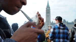 A protester lights a joint during a 4-20 marijuana rally on Parliament Hill in Ottawa on Friday, April 20, 2012. (Sean Kilpatrick / THE CANADIAN PRESS)