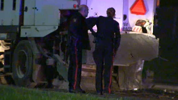 Police examine a street sweeper involved in a fatal crash on Shaganappi Trail early Tuesday morning.