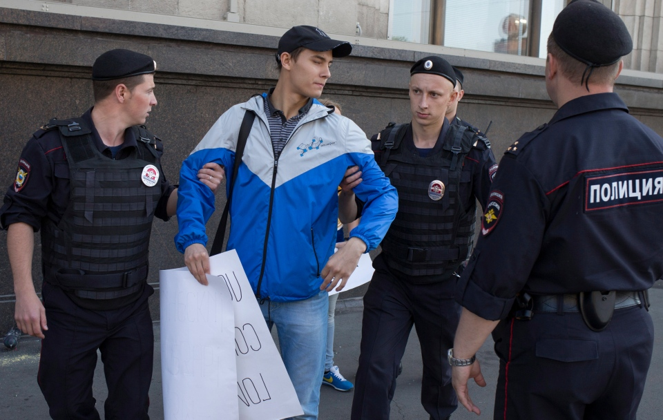 """Police officers detain a demonstrator supporting a law near the State Duma, Russia's lower parliament chamber, in Moscow, Russia, Tuesday, June 11, 2013. A controversial bill banning """"homosexual propaganda"""" is expected to be approved by Russia's lower house of parliament for the second and third of three hearings on Tuesday, June 11, 2013. (AP / Alexander Zemlianichenko)"""