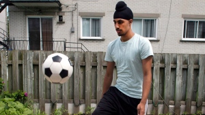 Aneel Samra, 18, plays with a soccer ball in his backyard, in Montreal on Wednesday, June 5, 2013. Samra has not been able to play organized soccer due to his religious headgear. (Ryan Remiorz / THE CANADIAN PRESS)