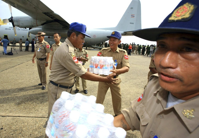 Burmese soldiers unload bottled water from a Thai transport plane at Yangon airport in Burma on Tuesday, May 6, 2008. (AP Photo)