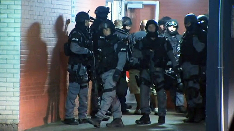 Heavily armed Toronto police officers conduct early-morning raids in west-end Toronto on Thursday, June 13, 2013.
