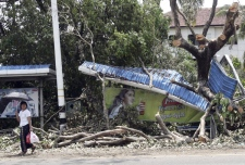 A girl makes her way past a bus station destroyed by a last weekend's cyclone in Yangon, Burma, Tuesday, May 6, 2008. (AP photo)