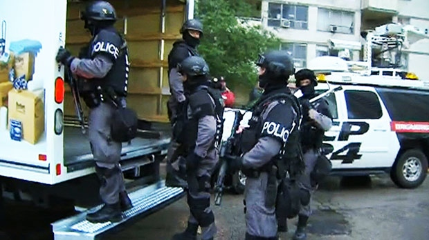 Heavily armed Toronto police officers conduct early-morning raids at 320 Dixon Road in west-end Toronto on Thursday, June 13, 2013.
