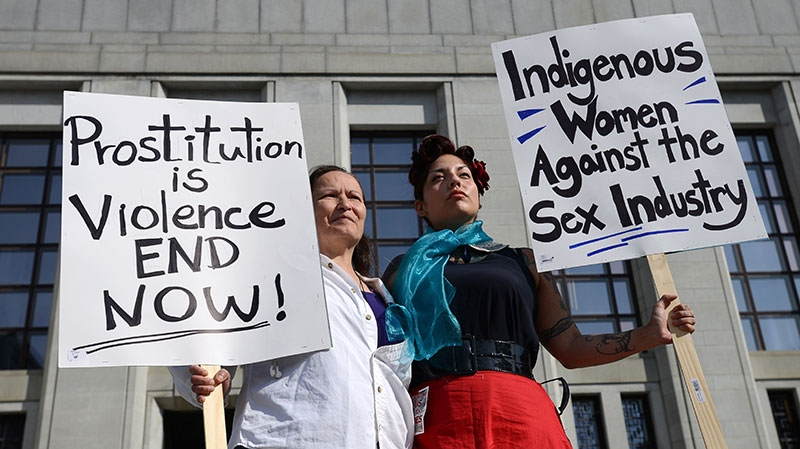Cherry Smiley, middle right, of Vancouver, B.C., and Sue Martin , left, of Ottawa join others as they rally in front the Supreme Court of Canada in Ottawa on Thursday, June 13, 2013. (Sean Kilpatrick / THE CANADIAN PRESS)