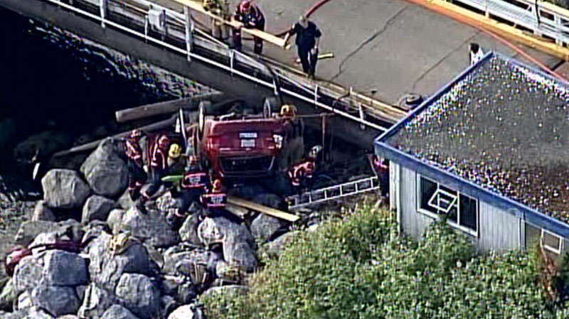 Firefighters surround a vehicle that crashed off the Village Bay ferry terminal on Mayne Island. June 13, 2013. (CTV/Chopper 9)