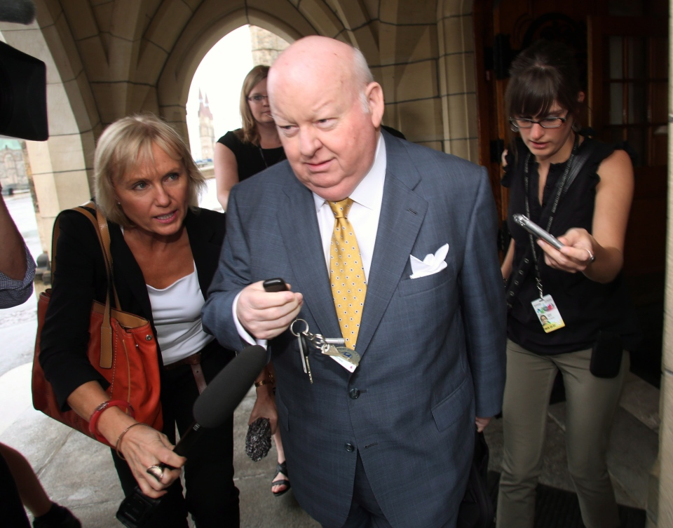 Sen. Mike Duffy is followed by reporters as he leaves Parliament Hill in Ottawa on Thursday, June 6, 2013. (The Canadian Press/Fred Chartrand)