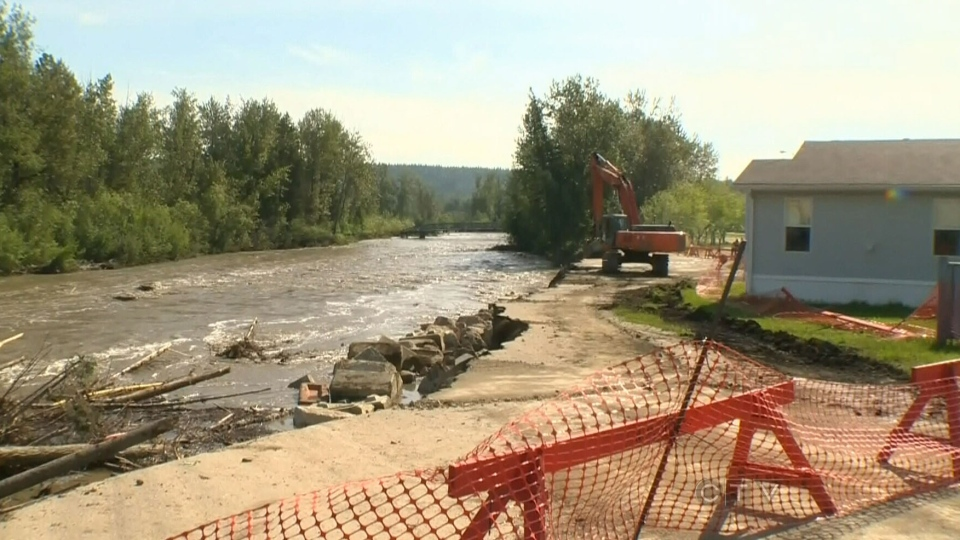 Heavy equipment is being used to drop concrete blocks in the water to form a protective barrier between the water and Ft. McMurray homes on Friday, June 14, 2013. (CTV Edmonton)