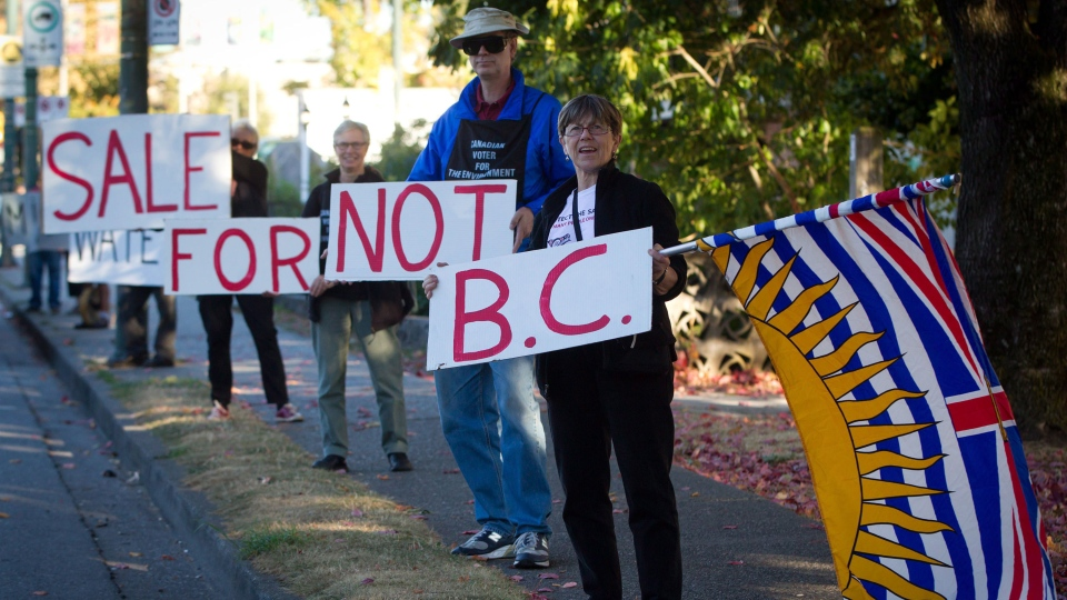 A group opposing the expansion of the Kinder Morgan Trans-Mountain pipeline hold up signs to passing motorists as the group Communities Against Pipelines protests in Vancouver, B.C., on Friday, Oct. 5, 2012. (Darryl Dyck / THE CANADIAN PRESS)