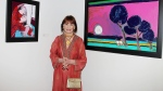 "This image released by Starpix shows fashion designer and artist Gloria Vanderbilt poses between two of her paintings at the ""1stdibs Presents: The Exhibition of The World of Gloria Vanderbilt"" preview party at 1stdibs Gallery, Wednesday, Sept. 12, 2012 in New York. (AP Photo/Starpix, Dave Allocca)"