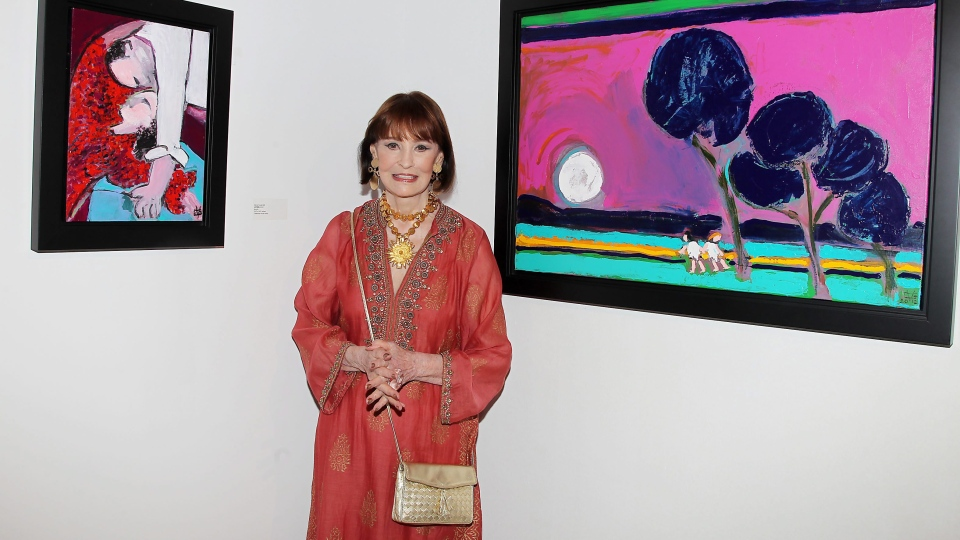 This image released by Starpix shows fashion designer and artist Gloria Vanderbilt poses between two of her paintings at the