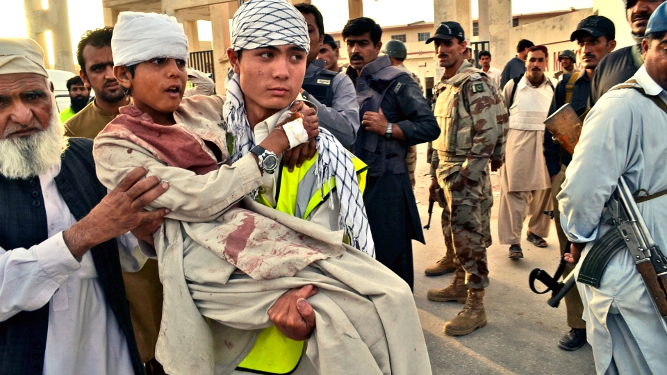A Pakistani boy who was injured by gunmen is carried to a vehicle outside a hospital in Quetta, Pakistan, Saturday, June 15, 2013.  (AP / Arshad Butt)