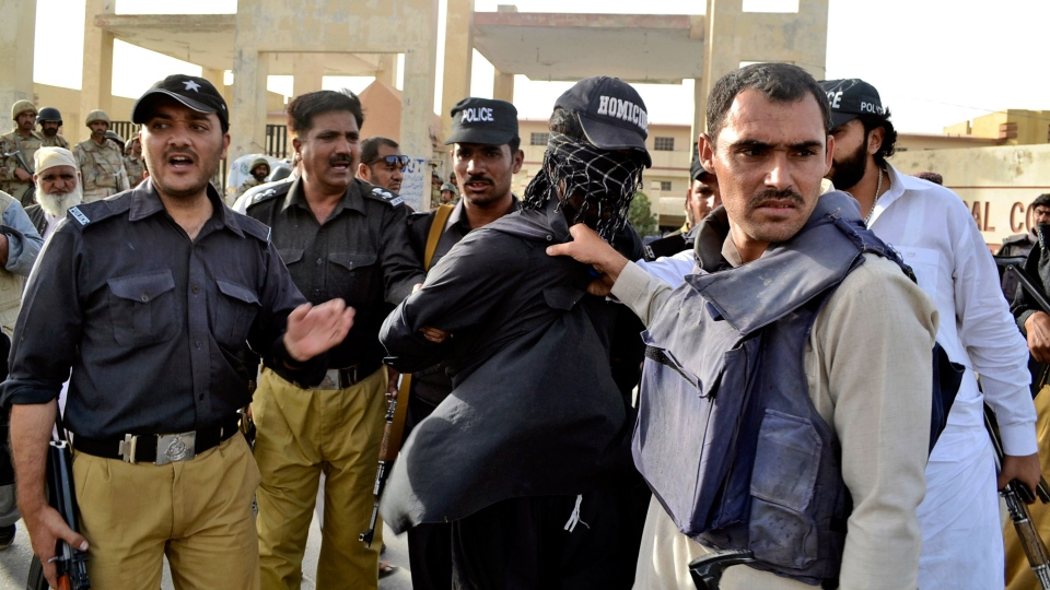 Pakistani police officers detain an alleged militant from the site of a gun battle at a hospital, in Quetta, Pakistan, Saturday, June 15, 2013. (AP / Arshad Butt)