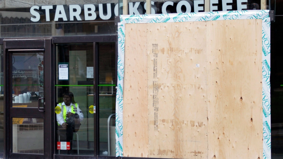 A security guard keep watch over a boarded up, vandalized, Starbucks Coffee in on Queen Street in downtown Toronto, Sunday, June 27, 2010. (AP / Carolyn Kaster)