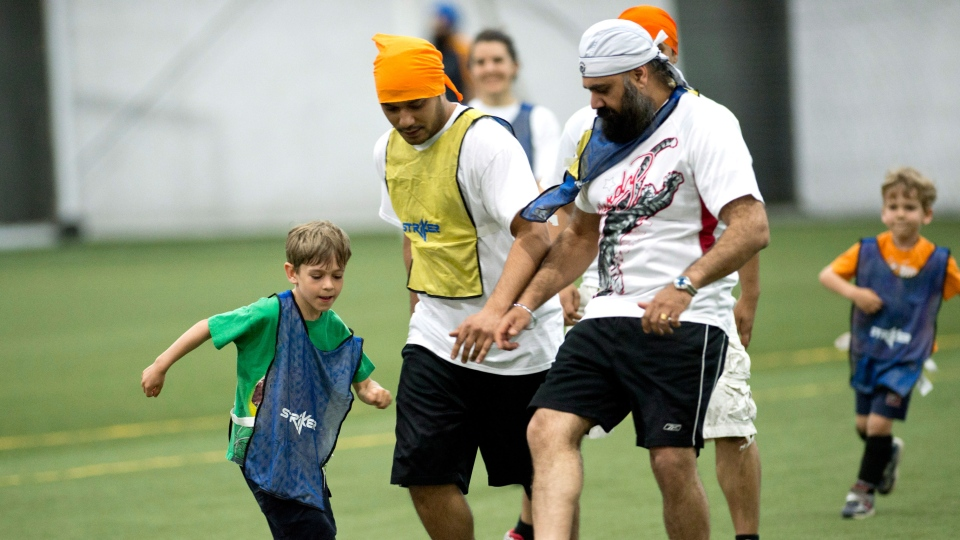A group of men and boys play a friendly soccer match in solidarity with young players who wear turbans in Montreal, Saturday, June 15, 2013. (Paul Chiasson / THE CANADIAN PRESS)