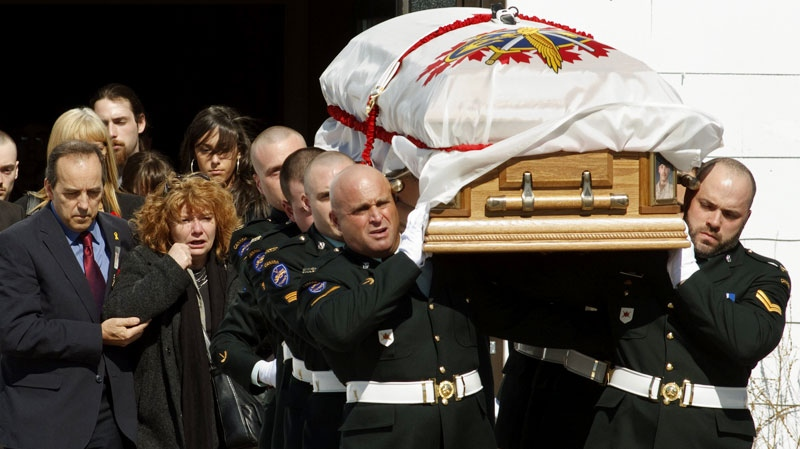 The casket bearing Cpl. Yannick Scherrer is carried out of the church following funeral services, as his father Guy Scherrer, left, and his mother Josee Belisle, second left, look on in CFB Valcartier on Friday April 8 2011. (Clement Allard / THE CANADIAN PRESS)