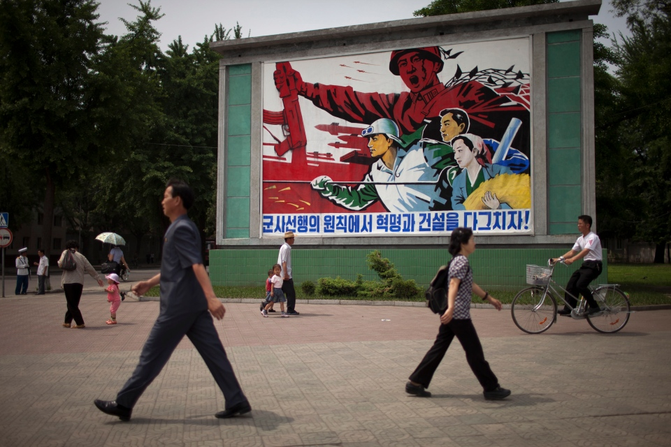 "People walk past a roadside propaganda billboard promoting the ""military first"" policy and a boost to build the country's economy in Pyongyang, North Korea, Sunday, June 16, 2013.  (AP / Alexander Yuan)"