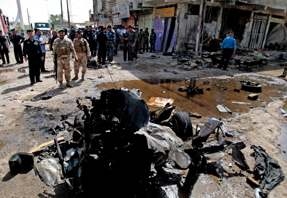 Iraqi security forces inspect the site of a car bomb attack in Basra, 340 miles (550 kilometers) southeast of Baghdad, Iraq, Sunday, June 16, 2013. Most of the car bombs hit Shiite-majority areas and were the cause of most of the casualties, killing tens. The blasts hit half a dozen cities and towns in the south and center of the country. (AP / Nabil al-Jurani)