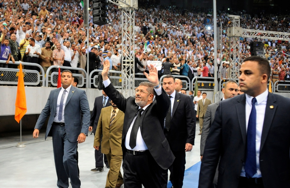 Egyptian President Mohammed Morsi waves as he arrives at a rally called for by hardline Islamists loyal to the Egyptian president to show solidarity with the people of Syria, in a stadium in Cairo, Egypt, Sunday, June 15, 2013. (AP / Egyptian Presidency)