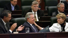 Alberta Premier Ralph Klein, centre, holds back tears as his colleagues, Education Minister Gene Zwozdesky, left, and Finance Minister Shirley McClellan, comfort him following a standing ovation at the end of his last day in the Alberta Legislature in Edmonton on Aug. 31, 2006. (Jeff McIntosh / THE CANADIAN PRESS)