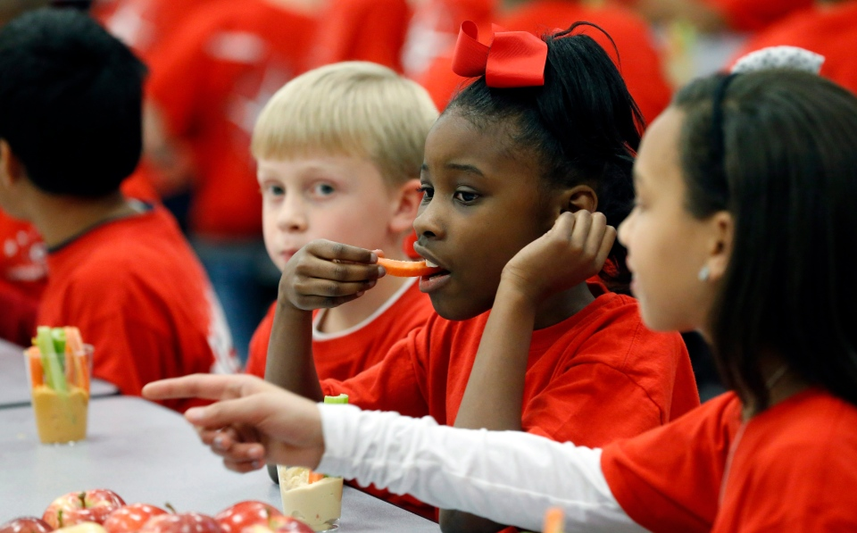Northside Elementary School student Jakiya Michael, 9, eats a carrot served in a hummus dip as her classmates watch at the Clinton, Miss., school, Wednesday, Feb. 27, 2013. (AP / Rogelio V. Solis)