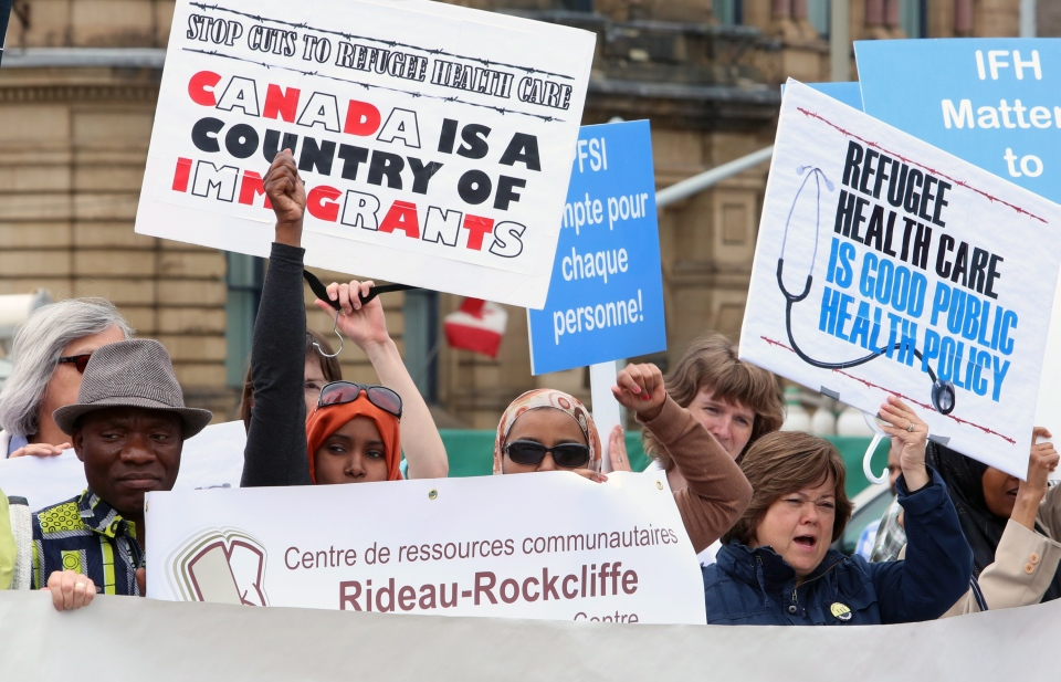 Supporters against federal government cuts to refugee health services protest on Parliament Hill in Ottawa, Monday, June 17, 2013. (Fred Chartrand / THE CANADIAN PRESS)