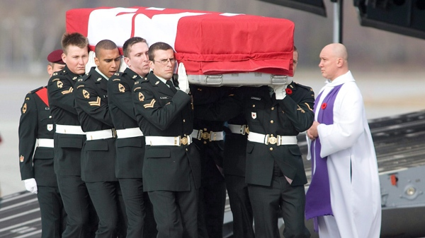 The casket containing the remains of Lt. Justin Boyes is carried from the aircraft past a military chaplain during a repatriation ceremony at CFB Trenton on Saturday Oct. 10, 2009. (Peter Redman / THE CANADIAN PRESS)