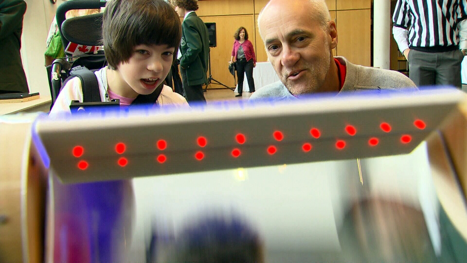Hillary Ball and her father Jim play with a student-designed panel that lights up when it detects motion.