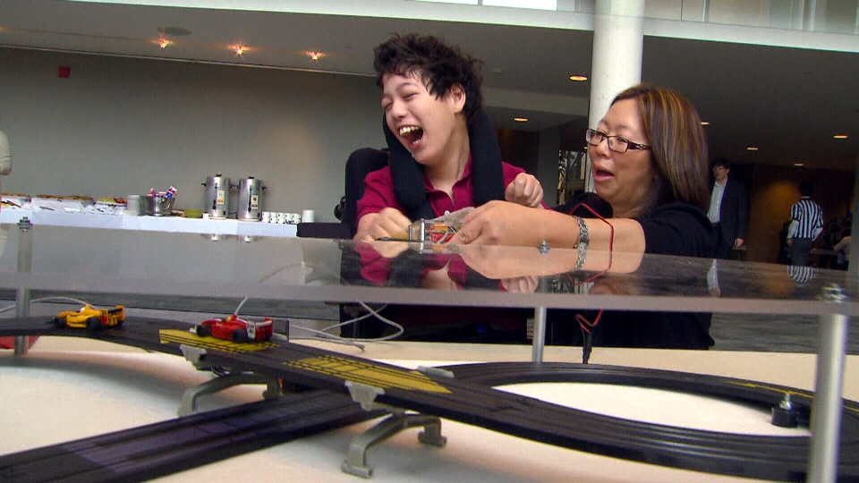 Thirteen-year-old Matthew Dowling and his mother Joanne check out a touch-controlled race car track made by students.