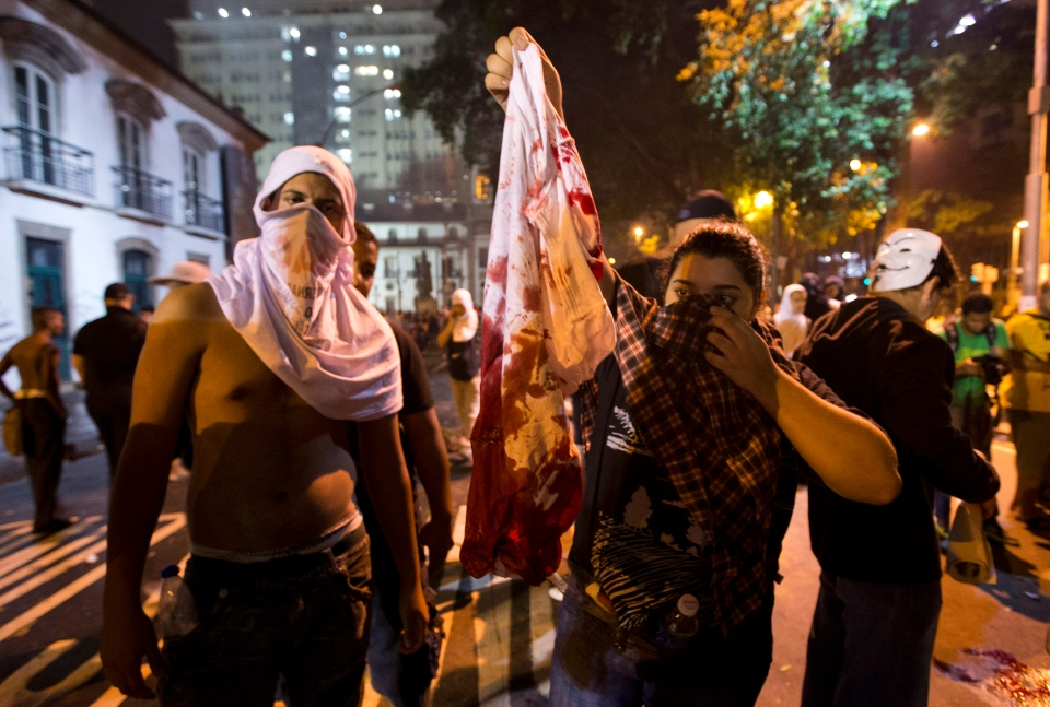 Protesters hold a blood-stained t-shirt of a protester that was shot in the shoulder during a demonstration in Rio de Janeiro, Brazil, Monday, June 17, 2013. (AP / Victor R. Caivano)