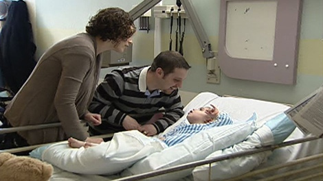 Parents Katy and Jimmy Ruggiero stand by the bed of their son Luca, recovering from injuries sustained in a car crash.