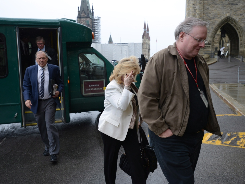 An unidentified man shields Sen. Pamela Wallin from media cameras as she arrives at the Senate entrance on Parliament Hill in Ottawa on Thursday, June 6, 2013. (The Canadian Press/Sean Kilpatrick)