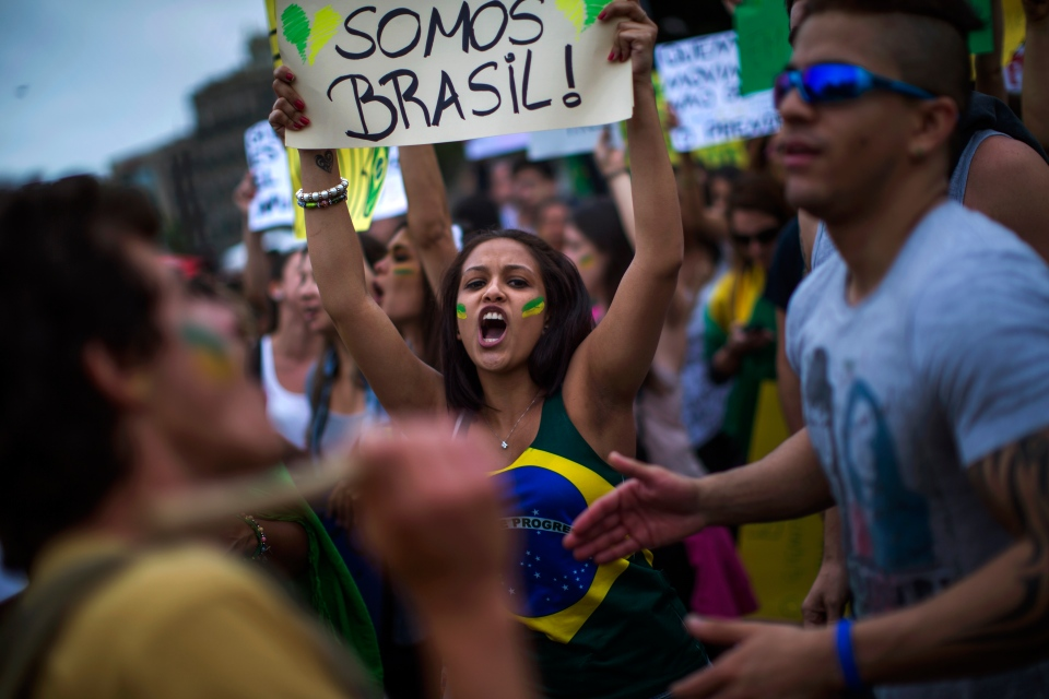 "Brazilian with spanish nationality Lorena Amgeluce, 22, holds a banner reading ""We are all Brazil"" during a demonstration in Barcelona, Spain, Tuesday, June 18, 2013. (AP / Emilio Morenatti)"