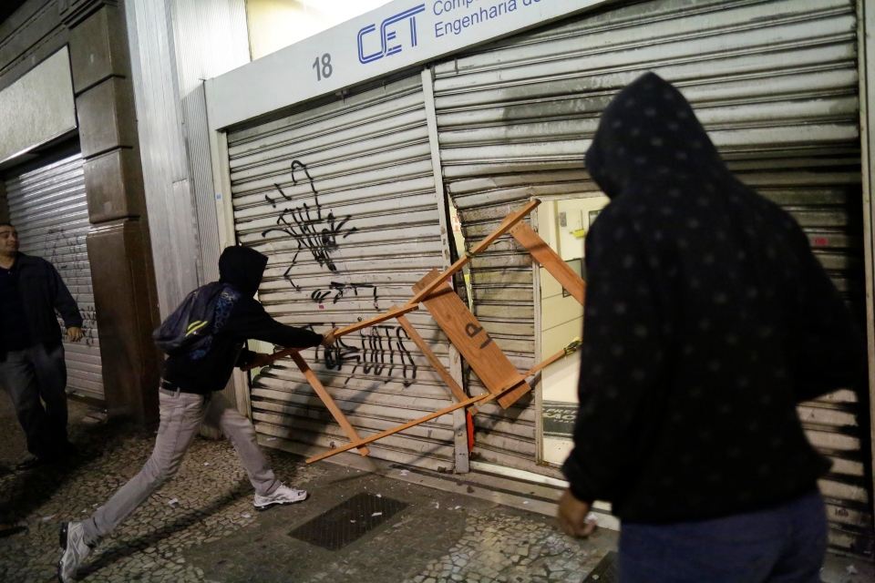 Protestors destroy a city traffic engineering center's security gate in Sao Paulo, Brazil, Tuesday, June 18, 2013. (AP / Nelson Antoine)