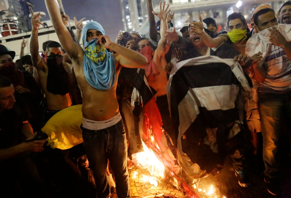Protestors burn a Sao Paulo state flag in front of City Hall, in Sao Paulo, Brazil, Tuesday, June 18, 2013. (AP / Nelson Antoine)
