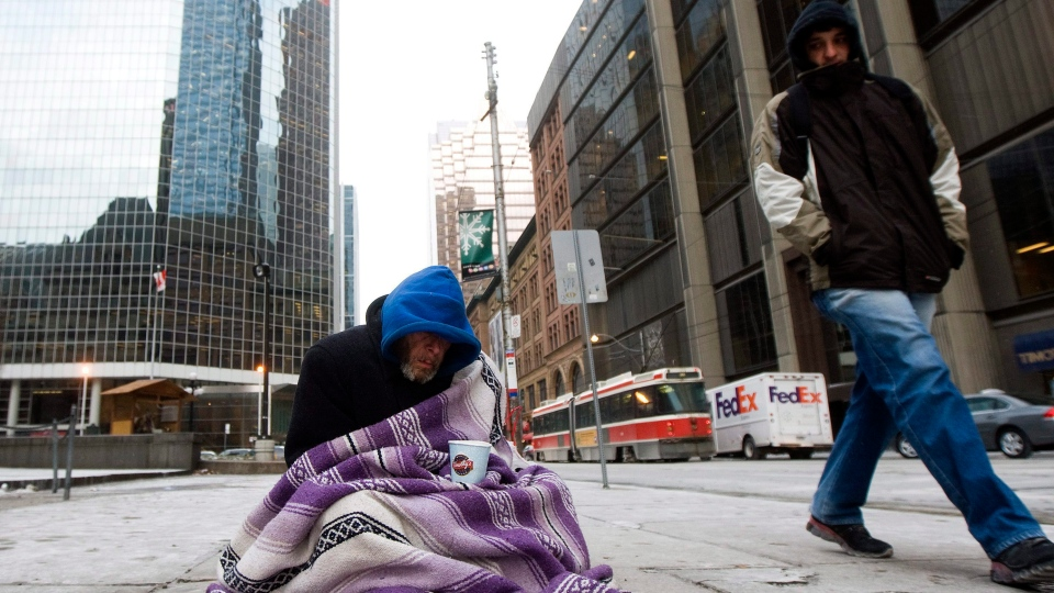A homeless person panhandles for money during an extreme cold weather alert for the City of Toronto on Monday, Dec. 13, 2010. (The Canadian Press/Nathan Denette)