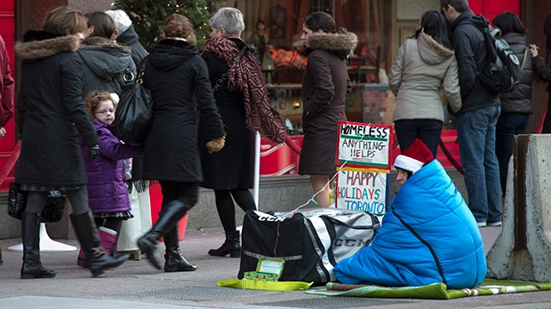 A homeless person sits on the sidewalk as holiday shoppers admire displays in the windows of a downtown department store in Toronto on Sunday, December 23, 2012. (Frank Gunn / THE CANADIAN PRESS)