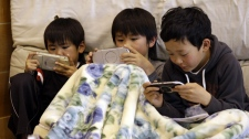 Children play games after taking a moment of silence at 2:46 p.m., exactly a month after a massive earthquake struck the area in Kamaishi, Iwate prefecture, Japan, Monday, April 11, 2011. (AP Photo/Lee Jin-man)