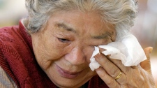 A survivor woman wipes her tear after she takes a moment of silence, exactly a month after a massive earthquake struck the area in Kamaishi, Iwate prefecture, Monday, April 11, 2011. (AP / Lee Jin-man)